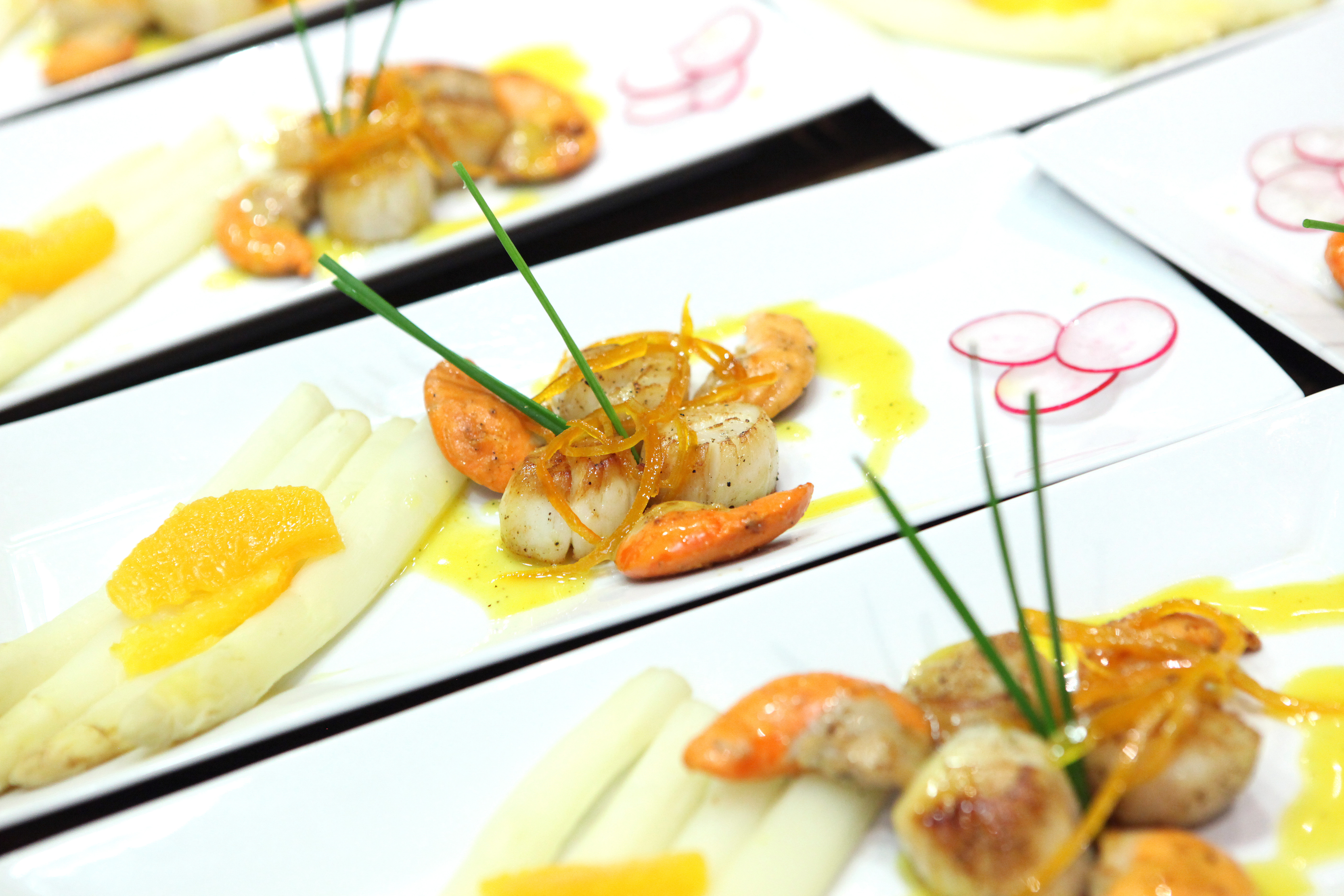 Scallops in orange butter sauce with candied citrus zest and white asparagus. Photo: Vincent Bourdon